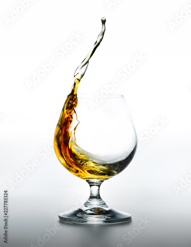 Tuinposter Alcohol Cognac glass with splashing brandy inside