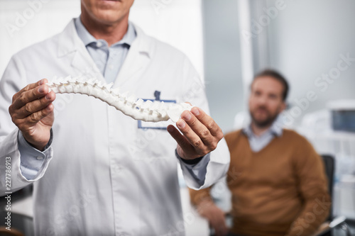 Fotografía  Close up of medical adviser explaining for male patient and showing how spine lo