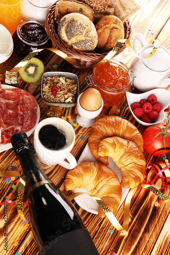 Fototapeta breakfast on table with bread buns, croissants, coffe and juice on new years eve obraz