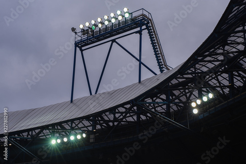 Fotografía  Floodlight mast with some lights on against dark blue sky
