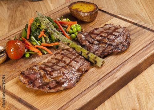 Staande foto Vlees Meat steak on the wooden board with vegetables