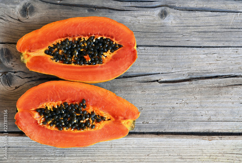 Fresh ripe organic papaya tropical fruit cut in half on old wooden background. Healthy eating,diet or vegan food concept.Selective focus.