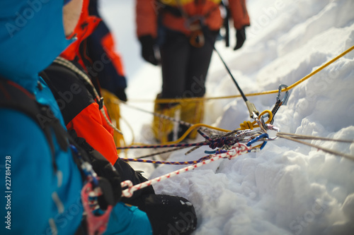 Photo sur Aluminium Alpinisme Fall protection mount climbers on the mountain slope, close-up. Tilt-shift effect.