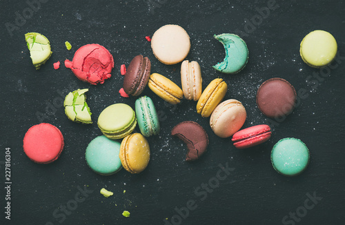 Fotobehang Macarons Flat-lay of sweet colorful French macaroon cookies variety over black background, top view