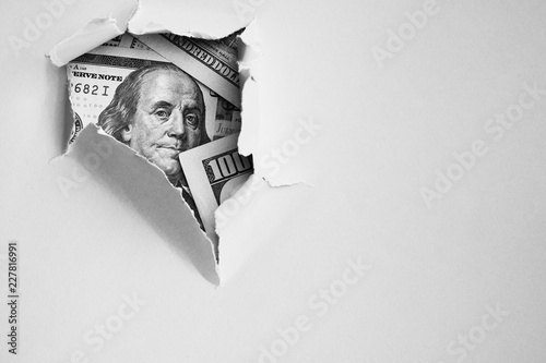 Photo Bill of one hundred dollars under holed paper