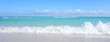 Turquoise clear ocean waves water splash on beautiful white sandy beach on blue sky with clouds background. Wide photo.