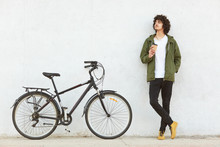 Horizontal Shot Of Male Cyclist Takes Break During Bike Ride, Drinks Takeaway Coffee, Dressed In Fashionable Clothes, Thinks About Something, Shows His New Modern Bicycle, Isolated On White Background