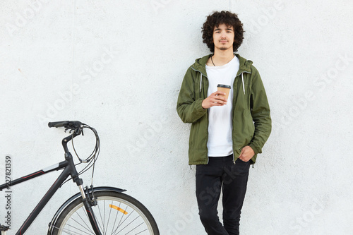 Fotografie, Obraz  Indoor shot of handsome guy with curly hair, dressed in fashionable jacket, black trousers, drinks hot beverage, stands near bicycle against white concrete wall