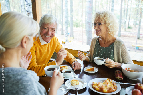 Fototapeta  Happy senior couple looking at their friend during conversation by cup of tea in