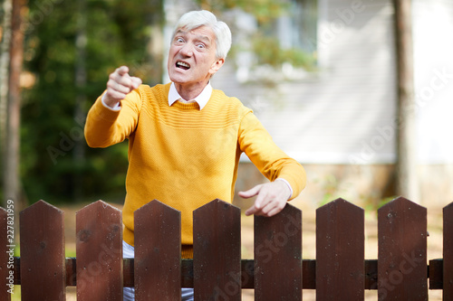 Angry senior man in yellow pullover standing by fence and pointing at you with a Tablou Canvas