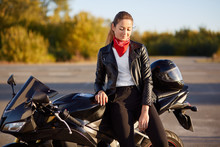View Of Good Looking Young Woman Dressed In Black Jacket, Has Stylish Red Bandana On Neck, Dark Hair Comed In Pony Tail, Stads Near Motorbike, Uses Helmet For Save Driving And Face Protection