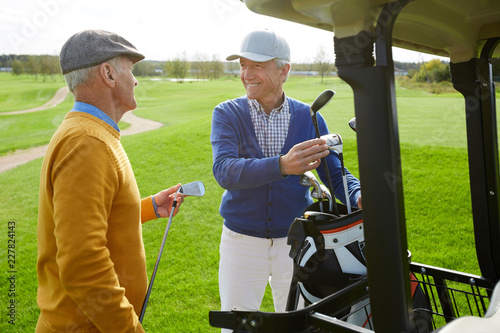 Photo sur Aluminium Golf Two cheerful aged buddies in pullovers and caps discussing the forthcoming game of golf while choosing clubs