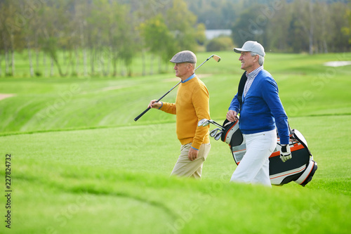 Two senior sportsmen with golf clubs walking along vast green field while hurrying for leisure game