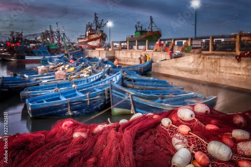 Plakat Maroko Essaouira portu w nocy. Selekcyjna ostrość na pierwszoplanowej czerwonej ryba kompensaci i pławikach. Tło ruchu plama kolorowe błękitne łodzie i seagulls w locie. Malownicza wioska rybacka.