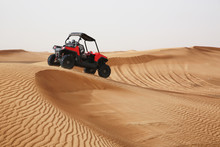 Off-road SUV Vehicle Speeding Through Sand Dunes In The Arabian Desert.