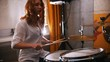Repetition. Redhead girl plays on drums. Slow motion. Focus on drums