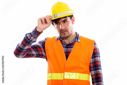 Studio shot of young Persian man construction worker thinking wh