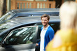 Happy young man in casualwear standing by car while going to leave for shopping in the city and looking at his wife