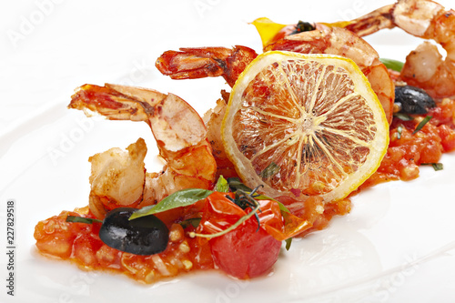 Close up of shrimps served with tomato sauces and slice of lemon.