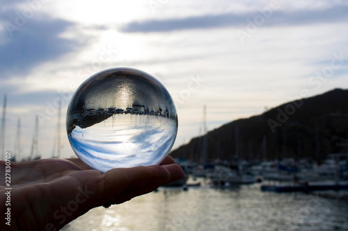 Photo  Early Morning over Harbor Ocean with Boats Captured in Glass Ball in Palm of Han