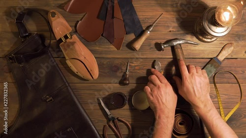 men's hands take tools for making shoes lie with a wooden table. The set of objects that symbolize manual labour, small business