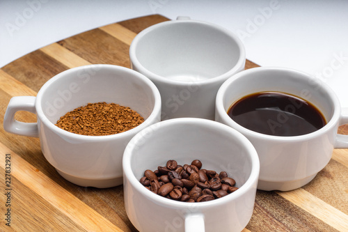 Fotobehang Cafe assortment of four white cups of coffee on a saucer grain, instant, brewed and an empty cup on the wooden surface background