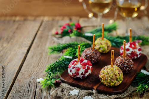 Variation of goat cheese balls appetizer with pistachio, pomegranate and flax seeds