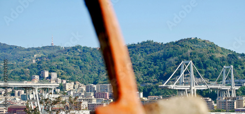 Poster Bridges A out of focus pickaxe with a not collapsed part of the Morandi bridge in the background. The structure is located in Italy, in the city of Genoa.