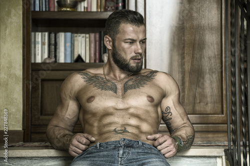 Vászonkép Portrait of sexy shirtless muscular man sitting on stair steps during the day, w