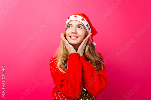 cf521e8808e5d A beautiful cute girl in a Santa Claus hat and with tinsel on her neck