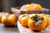 Ripe persimmon fruit in a basket on wooden background, healthy fruit