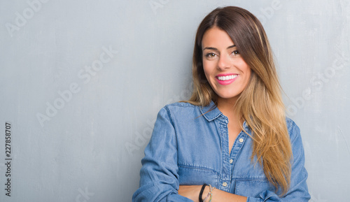 Photo  Young adult woman over grunge grey wall wearing denim outfit happy face smiling with crossed arms looking at the camera