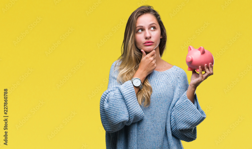 Fototapety, obrazy: Young beautiful blonde woman holding piggy bank over isolated background serious face thinking about question, very confused idea