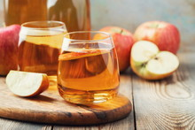 Organic Apple Cider Or Juice On A Wooden Table. Two Glasses With Drink And Autumn Leaves On Rustic Background