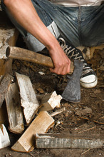Axe In Men's Hands And Chopped Wood