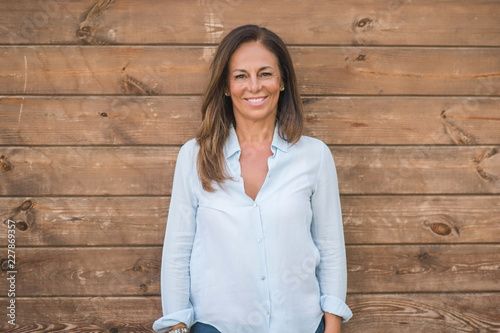 Fotografie, Obraz  Beautiful middle age hispanic woman at over wood wall on a sunny day with a happ