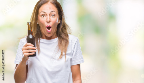 Middle age hispanic woman drinking beer over isolated