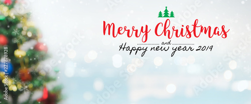 Fototapeta  Christmas and Happy new year 2019 on blurred bokeh christmas tree banner background with snowfall
