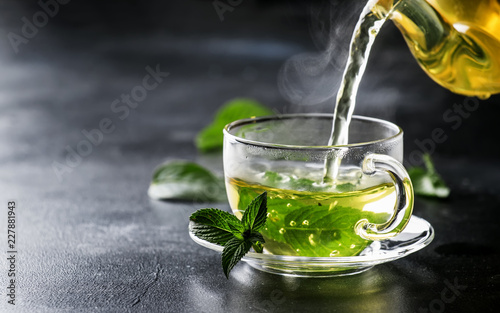 Photo Hot chinese green tea with mint, with splash pouring from the kettle into the cu