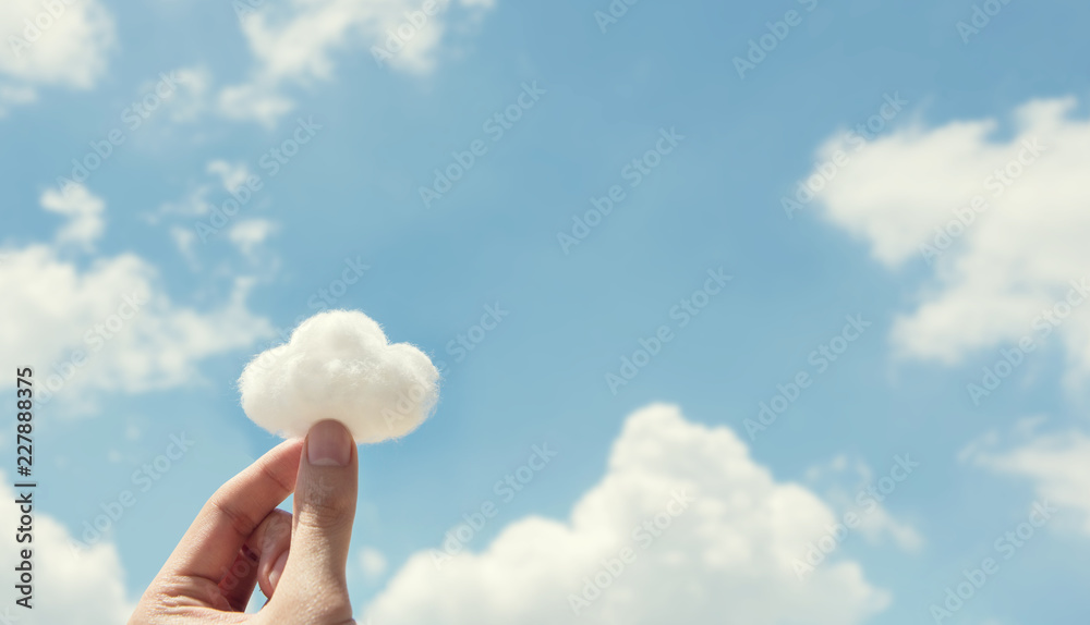 Fototapeta Woman hand holding cotton wool on cloud sky background. The development of the imagination, copy space.