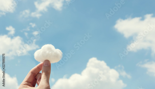 Obraz Woman hand holding cotton wool on cloud sky background. The development of the imagination, copy space. - fototapety do salonu
