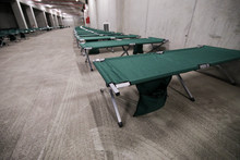 Camp Folding Cots Are Being Set Up In The Underground Parking Of A Stadium