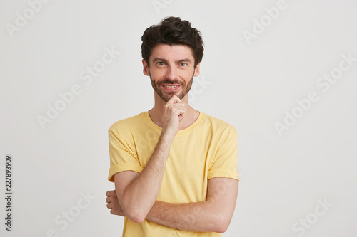 570e046012 Studio shot of a smiling attractive young man wearing yellow classic tshirt  looks happy and friendly