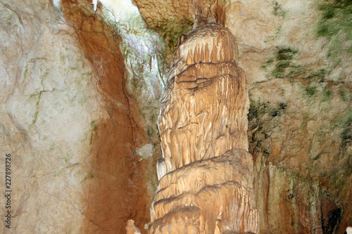 Natural texture photo of wonderful natural cave with fox-coloured walls and formations of stalagmites and stalactites in it