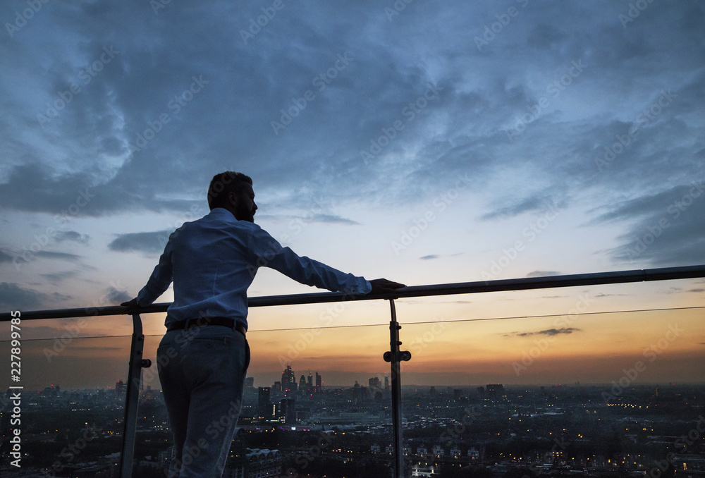 Fototapety, obrazy: A rear view of businessman standing against London view panorama at dusk.