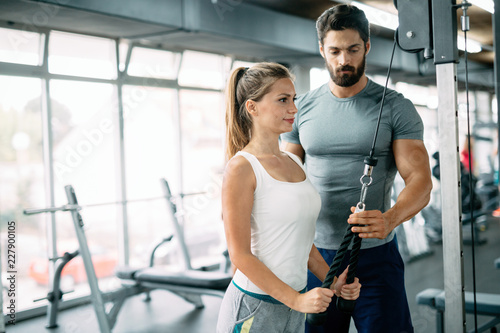 Personal trainer assisting beautiful woman lose weight Fototapeta