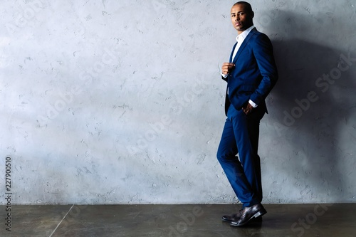 Fotografie, Obraz  Full length smiling business man in black suit looking at camera and standing isolated on gray background