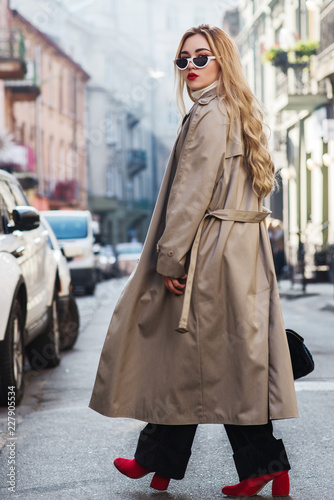 Outdoor full body fashion portrait of young beautiful fashionable woman wearing trendy beige long trench coat, stylish sunglasses, black trousers, red boots, model walking in street of european city Wall mural