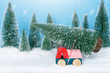 Miniature truck carrying a christmas tree with pine forest on the snow in winter. Christmas holiday celebration and new year concept