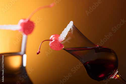 Alcohol layered shot cocktail garnished with cherry and sugar.